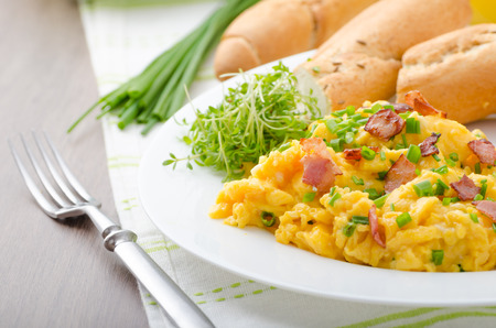 eggs and bacon: Scrambled eggs with bacon, chive and tomatoes, fresh juice and little microgreens healthy salad Stock Photo