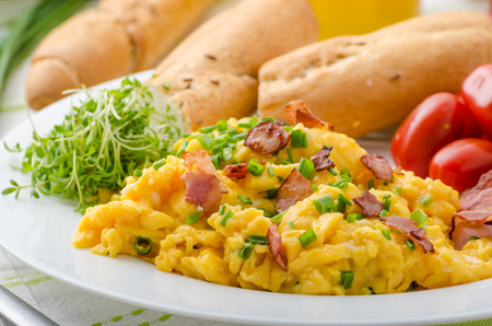 Scrambled eggs with bacon, chive and tomatoes, fresh juice and little microgreens healthy salad 스톡 콘텐츠