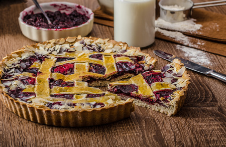 sprinkled: Shortbread tart with cherries, with beautiful grid, sprinkled with almonds