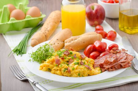 Scrambled eggs with bacon, chive and tomatoes, fresh juice and little microgreens healthy salad Standard-Bild