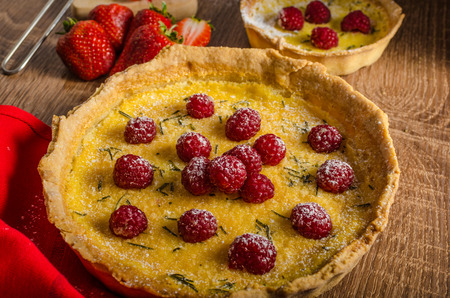 Lemon tart with rosemary and berries, filled with cream topped berries photo