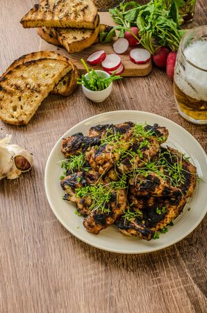 original plate: Grilled teriyaki chicken wings with chive and microgreens on top, garlic toast with fresh herbs and czech beer