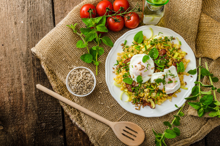 Spring salad from lentils, fresh herbs, baked nuts and on the top delicious poached egg