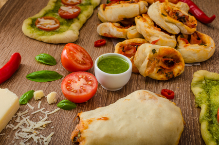 Variantion of pizza - with herbs pesto and tomatoes, calsone pizza and pizza rolls photo