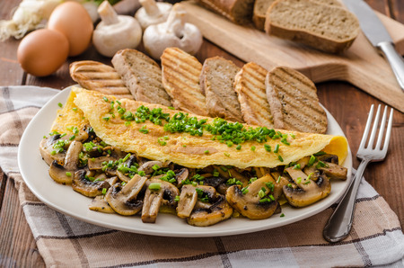 Rustic omelette with mushrooms on chives, roasted panini health bread