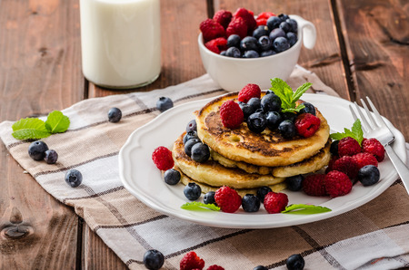 Pancakes with forest fruit and mint, fresh fruits and milk Standard-Bild