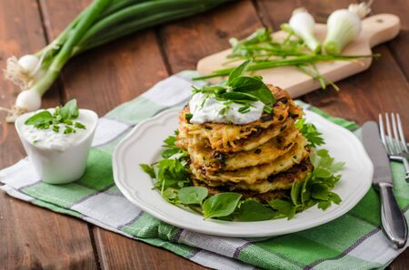 cheesy: Homemade potato pancakes with fresh cheesy dip with herbs and spring onion Stock Photo