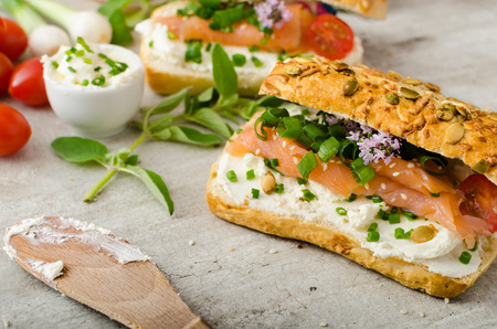 wholemeal baguette with cream cheese, seeds and smoked salmon with fresh herbs