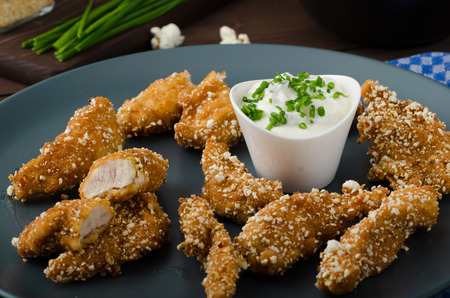 Chicken strips in popcorn breadcrumbs, with delicious garlic dip and panini toast photo