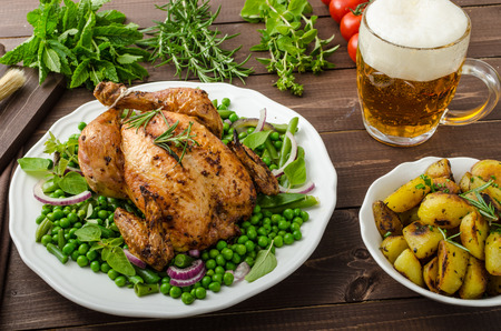 original plate: Grilled organic bio chicken, roasted potatoes, with spring vegetable and herbs, with beer Stock Photo
