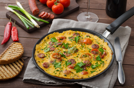 Omelette with chorizo sausage, herbs and tomatoes Standard-Bild