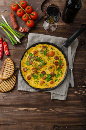 Omelette with chorizo sausage, herbs and tomatoes Stock Photo