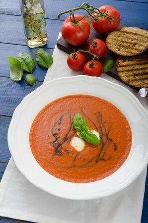 Tomato soup with mozzarella, balsamic winegrad and basil, bruschetta toasts photo