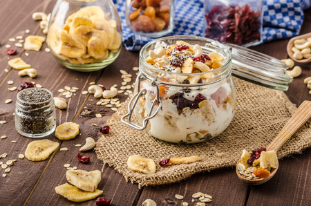 Homemade yogurt with granola, dried fruit and nuts with cia seed, apricot and banana dried fruit