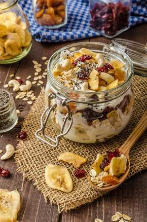 CIA: Homemade yogurt with granola, dried fruit and nuts with cia seed, apricot and banana dried fruit