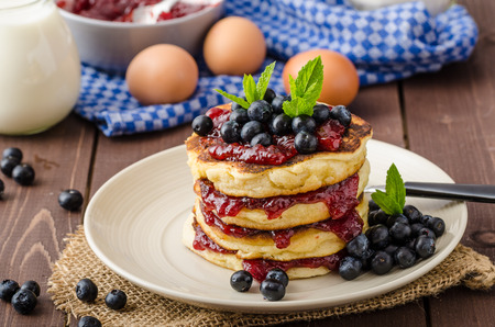 Glutten-free pancakes with jam and blueberries, fresh mint on top Imagens
