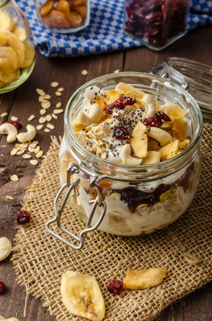 Homemade yogurt with granola, dried fruit and nuts with cia seed, apricot and banana dried fruit photo