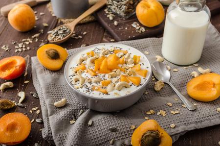 musli: Domestic apricots musli yogurt with milk and crispy nuts and healthy seeds chia Stock Photo
