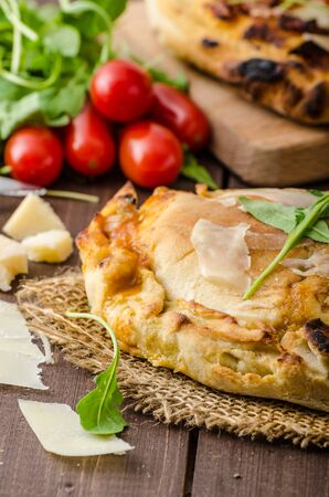 Calzone pizza, filled herbs, cheese and tomatoes photo