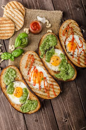Variaties van gebakken eieren in brood, panini brood met pesto en hete saus sriracha
