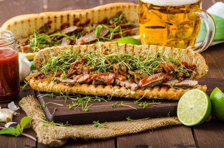 steak sandwich: Steak sandwich with herbs, lime and microgreens with little bit kick of hot sriracha sauce