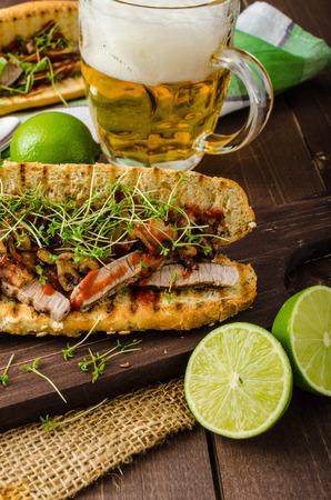 steak sandwich: Steak sandwich with herbs, lime and microgreens