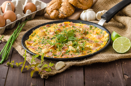 an omelette: Egg omeletta with ham and herbs, bio eggs and little bit of lime juice