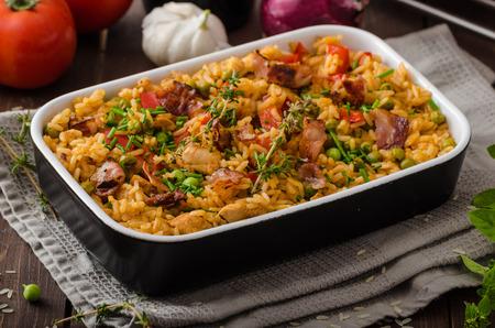 Cajun kip met rijst, vol van smaak en hete kruiden met verse groenten bio erwten Stockfoto