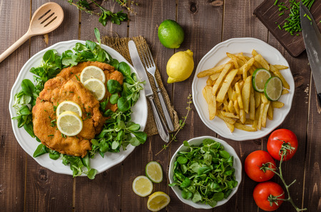 German schnitzel with homemade fries, lemons and limes, tomatoes and lambs lettuce salad