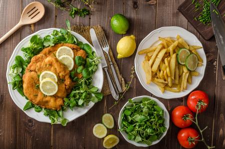 Schnitzel allemand avec frites maison, citrons et limes, les tomates et salade de l'agneau Banque d'images - 42065627
