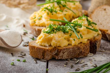 huevos revueltos: Huevos revueltos con hierbas de trigo-centeno crujiente pan, hecho en casa Foto de archivo