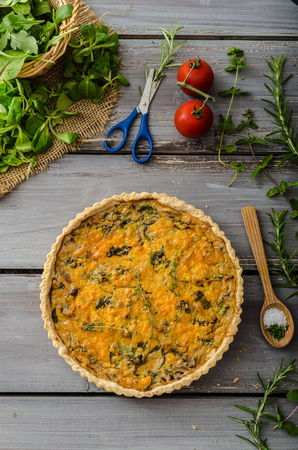 Domestic rustic quiche, filled onion herbs, garlic and salad. Stock fotó