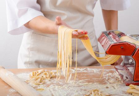 Jonge vrouw chef-kok bereidt zelfgemaakte pasta van bloem durumgriesmeel