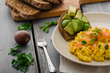 eggs and bacon: Scrambled eggs with smoked salmon and whole wheat toast with avocado and lemon Stock Photo