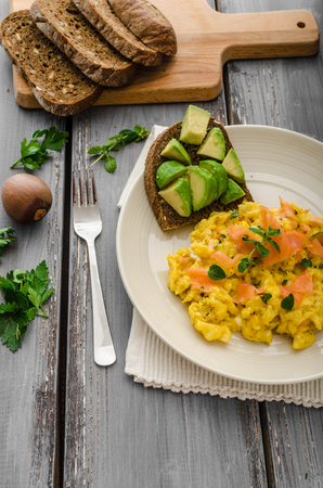 wheat toast: Scrambled eggs with smoked salmon and whole wheat toast with avocado and lemon Stock Photo