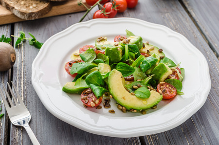 extra virgin: Summer salad of avocado, tomato, peanuts and lamb lettuce salad, whole grain bread and topped extra virgin olive oil Stock Photo