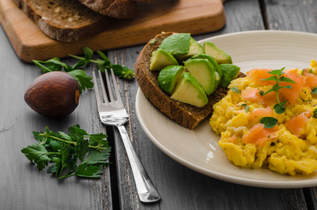 Scrambled eggs with smoked salmon and whole wheat toast with avocado and lemon Stock Photo