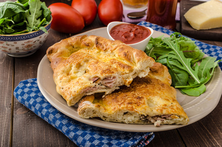 Calzone pizza stuffed with cheese and prosciutto, hot dip and summer lettuce salad
