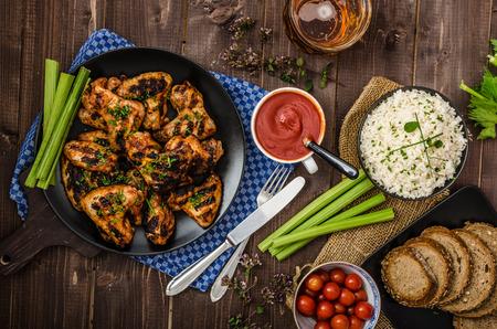 arroz: Alas a la parrilla de pollo con salsa de chile picante, pan al horno con semillas, arroz jazmín con las hierbas y la cerveza