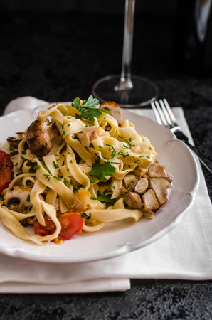advertisment: Pasta with roasted garlic and mushrooms, roasted garlic on oven, glass of wine, place for advertisment Stock Photo