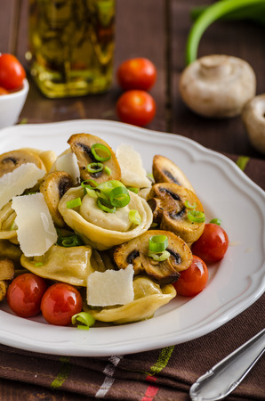 stuffed tortellini: Homemade tortellini stuffed with mushrooms and spring onion, roasted tomatoes, garlic souce, topped parmesan Stock Photo