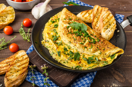 Herb omelette with chives and oregano sprinkled with chili flakes, garlic panini toasts Standard-Bild