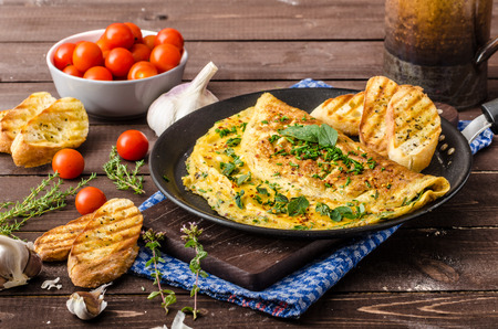 Herb omelette with chives and oregano sprinkled with chili flakes, garlic panini toasts Archivio Fotografico