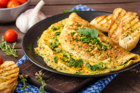Herb omelette with chives and oregano sprinkled with chili flakes, garlic panini toasts Imagens