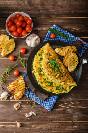 breakfast plate: Herb omelette with chives and oregano sprinkled with chili flakes, garlic panini toasts Stock Photo