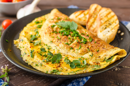 Herb omelette with chives and oregano sprinkled with chili flakes, garlic panini toasts 免版税图像