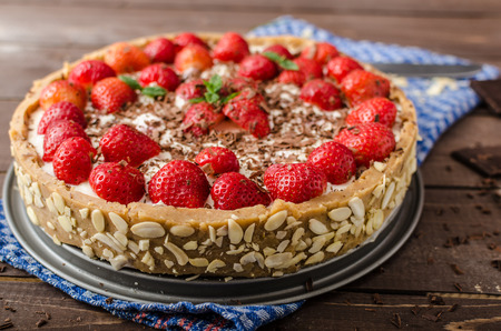 chocolate shavings: Summer strawberry cheesecake stuffed by nuts and almonds, topped with chocolate shavings Stock Photo