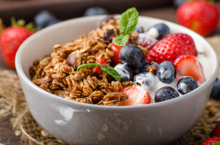 Yogurt with baked granola and berries in small bowl, strawberries, blueberries. Granola baked with nuts and honey for little sweetness. Homemade yogurt