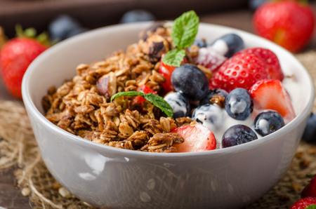 Yoghurt met gebakken muesli en bessen in een kleine kom, aardbeien, bosbessen. Muesli gebakken met noten en honing voor weinig zoetigheid. zelfgemaakte yoghurt