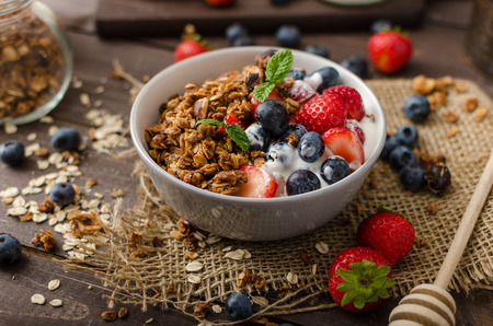 Yogurt with baked granola and berries in small bowl, strawberries, blueberries. Granola baked with nuts and honey for little sweetness. Homemade yogurt Imagens - 43567211